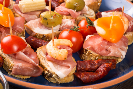 Set of canapes with ham, prawn, tomato and olives on blue plate