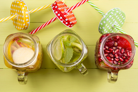 infused: Fresh fruits flavored water healthy detox drinks in jars - top view Stock Photo