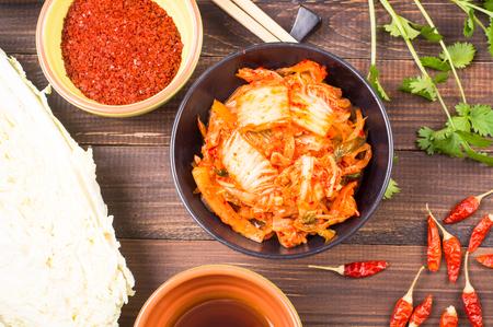 キムチ - 韓国のスーパー フード。木製テーブルの上のボウルに白菜のお漬け物