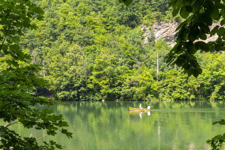 Green Hamori lake in Lillafured near Miskolc, Hungary. Springtime landscape in Beech Mountains with unrecognisable people on boat Banco de Imagens