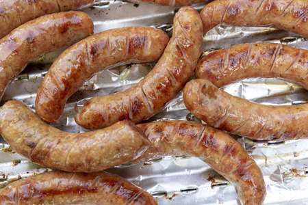 Pork sausages on an aluminium tray on a grill. Top view Banco de Imagens