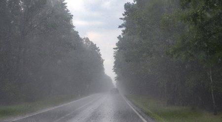 Asphalt road during very heavy rain. View through front windscreen of car