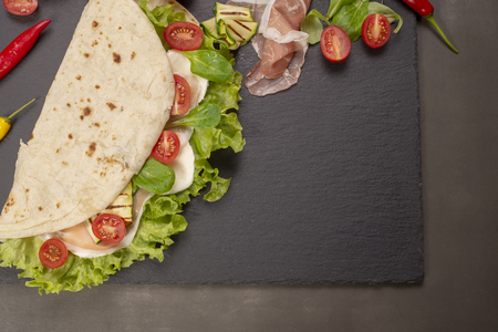 Italian piadina romagnola flatbread with lettuce, cherry tomatoes, prosciutto ham, mozzarella cheese and grilled zucchini