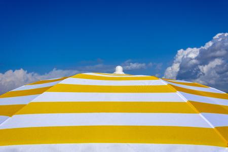 White and yellow sun umbrella on blue sky. Summer holiday Banco de Imagens