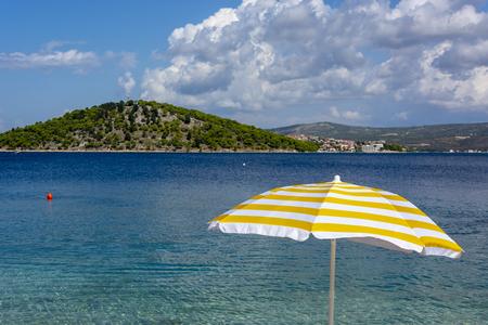 White and yellow sun umbrella on coast od Adriatic sea. Summer holiday in Croatia. Banco de Imagens