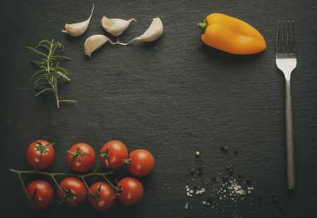 Black slate plate with tomatoes, pepper, garlic, rosemary, fork and spices. Copy space for menu. Vintage effect.