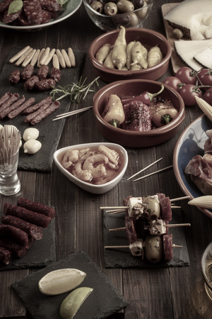 Mixed appetizers on wooden table. Spanish tapas for new years eve. Vintage effect Banco de Imagens