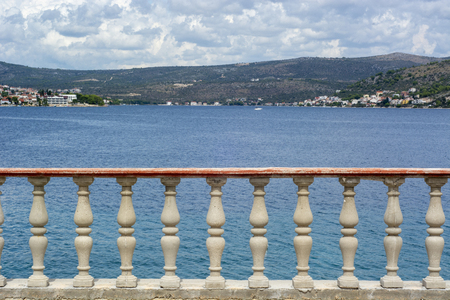 View of the concrete balustrade of the terrace on Adriatic Sea and village of Rogoznica, Croatia
