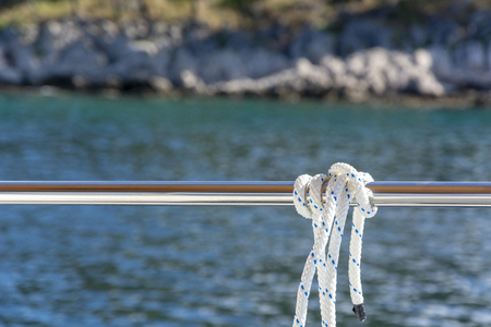 White and blue rope tied up on the yacht's railing with blurred background