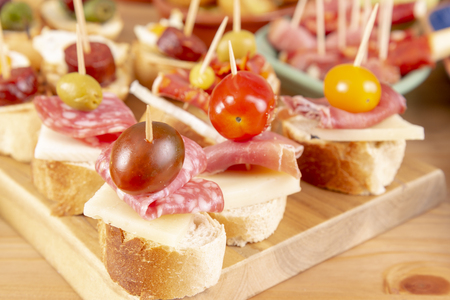 Open sandwiches with salami, pepper, cheese and olives. Mediterranean tapas snacks.