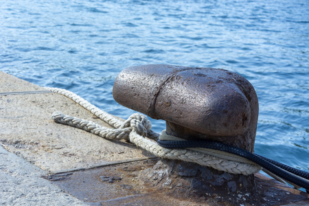 Old iron mooring bollard with black and white ropes