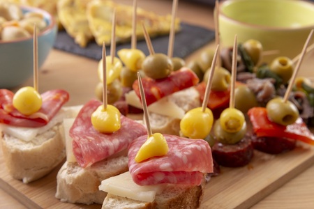 Open sandwiches with salami, pepper, cheese and olives. Mediterranean tapas snacks. Banco de Imagens - 119870892