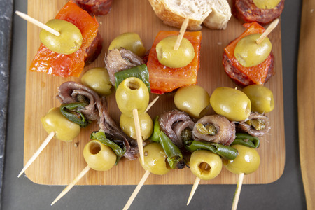 Top view of Spanish tapas snacks with olives, anchovies and peppers Banco de Imagens
