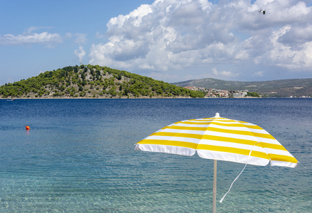 White and yellow sun umbrella on coast od Adriatic sea. Summer holiday in Croatia. Banco de Imagens