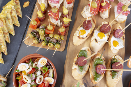 Top view of Spanish tapas snacks with olives, anchovies, tortilla, patas and peppers Banco de Imagens