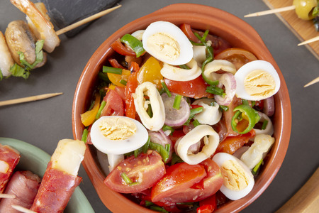 Top view of Spanish tapas snacks with olives, squid, anchovies and peppers Banco de Imagens - 119870896