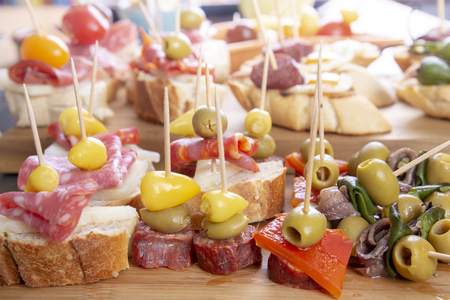 Sharing mixed spanish tapas starters on table. Olives, sandwiches and bread