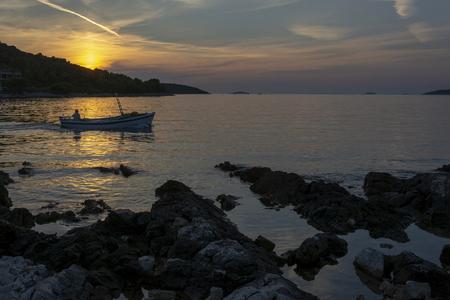 Fishing boat and romantic sunset on the Adriatic bay in Croatia near Rogoznica Banco de Imagens