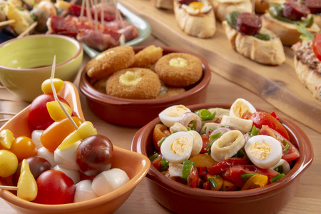 Small appetizers on skewers with cheese, olives and sausage. Tapas or antipasto food