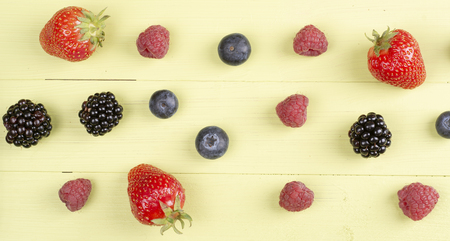 Soft fruits like strawberry, raspberry, blackberry on a green wooden table. Top view Banco de Imagens