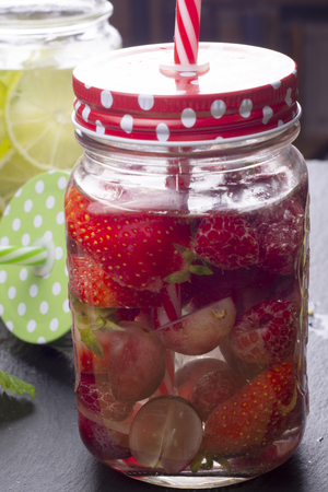 Fresh cold water with strawberry and raspberry in glass jar Banco de Imagens