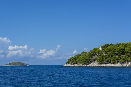 Old little church on peninsula in Rogoznica Croatia and sea water and little island on Adriatic sea Banco de Imagens