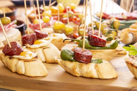 Small appetizers on skewer with cheese, olives and sausage. Spanish tapas or italian antipasto food