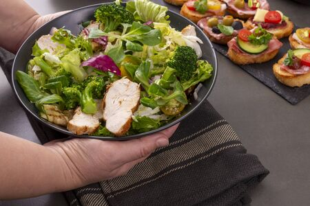 Hands serving plate with grilled chicken, lettuce and broccoli salad Banco de Imagens