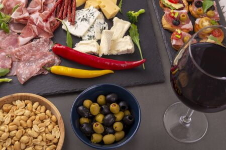Various snacks - ham, olives, peanuts on the grey table. View from above Banco de Imagens