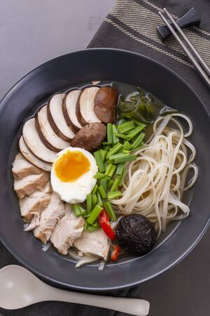 Japanese ramen soup with chicken, mushrooms, pasta, egg and chives on a black background. Top view