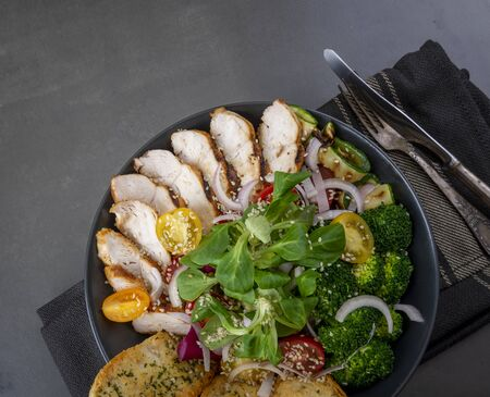 Salad of grilled chicken breast with broccoli, tomatoes and lamb's lettuce on a dark table. Variety of Caesar salad. Flat lay and copy space