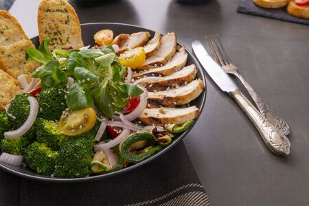 Plate with grilled chicken, lettuce and broccoli salad with toasts.