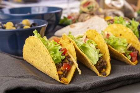 Three fresh tacos with beef, corn, tomatoes and lettuce. Mexican cuisine