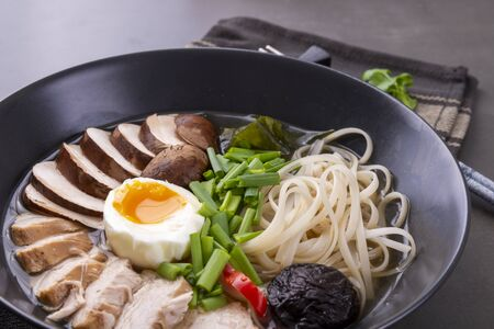 Japanese ramen soup with chicken, mushrooms, pasta, egg and chives on a black background
