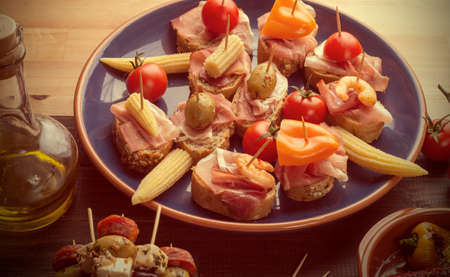 Variety of Mediterranean snacks on blue plate. Tapas or antipasti. Vintage effect