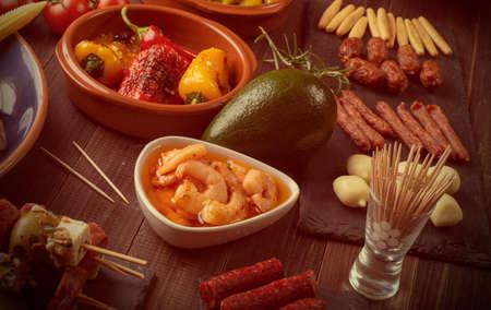 Variety of Mediterranean snacks on old wooden table. Tapas or antipasti. Vintage effect
