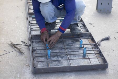 Workers are using steel pliers to clamp the wire in order to twist to fasten the blue PVC tube strand to the steel frame laid for making a pattern for making cement pipe caps.