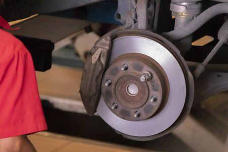 El mecánico está limpiando el juego de frenos de la rueda delantera del automóvil antes de cambiar a una rueda nueva. Foto de archivo