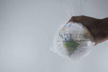Globe is wrapped in plastic on hand of human . Show the environmental problem with the pollution of the earth with plastic and warming due to greenhouse effect.