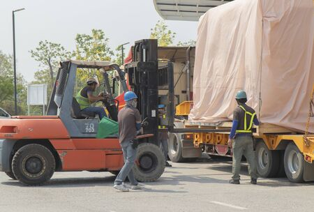 Orange forklift is lifting train head for driving simulation , covering the pink cloth, move from yellow truck. Concept team work  leader,  electric train industry work