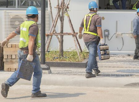 Workers are carrying steel wheels for very heavy loads. Move the electric train into the building In order to install the driving simulation 스톡 콘텐츠