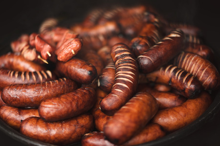 Mix of hot grilled sausages prepared on a street market. Close up.