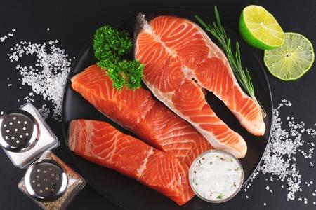 Bouchent la vue de dessus des steaks de saumon cru frais avec citron vert, verts, sauce et épices sur fond noir. Banque d'images
