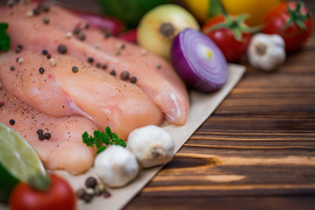 Close up of fresh raw chicken fillet with grens and vegetables. Concept of healthy eating. Mock up, copyspace for your text.