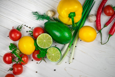 Mix of fresh bright fruits and vegetables on the white wooden background.