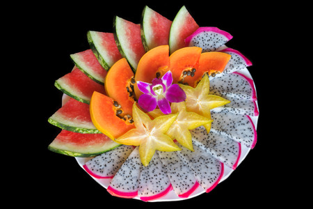 Top view of sliced tropical friut mix: papaya, watermelon, dragon fruit, carambola isolated on black background. Stock Photo