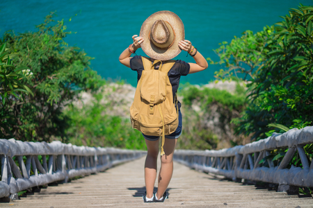 Young european female tourist with a backpack and bamboo cowboy style hat going down the stairs to the beach. Stock Photo