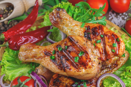 flesh eating animal: Close up of hot grilled chicken drumsticks with fresh vegetables, greens and spices on rustic wooden background. Stock Photo