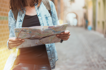 Young european female tourist with a backpack standing on a narrow street and checking the map with city sights looking for the next place to go. Travel and freelance concept. Copy space for your text.