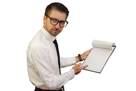 Young business consultant pointing at notepad with blank sheet frowning and looking stricktly. Isolated on white background. Mock up, copy space for your text.